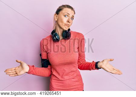Beautiful caucasian woman wearing sportswear and arm band clueless and confused expression with arms and hands raised. doubt concept.