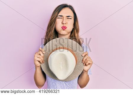 Young hispanic girl wearing summer hat covering mouth puffing cheeks with funny face. mouth inflated with air, catching air.