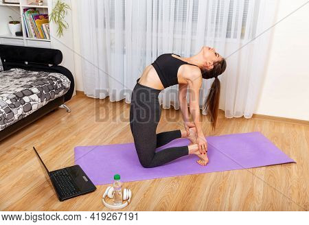 Young Sports Girl Do Sports At Home Online With A Laptop, Sportswoman Does Exercise In The Room. Hom