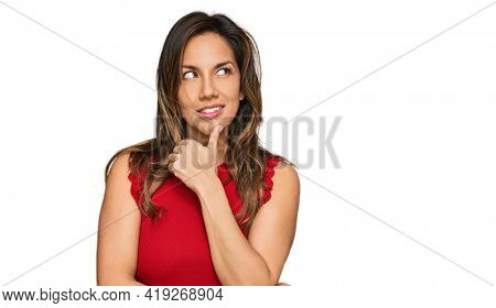 Young hispanic woman wearing casual clothes with hand on chin thinking about question, pensive expression. smiling with thoughtful face. doubt concept.