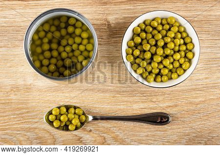 Opened Metallic Jar, White Glass Bowl With Canned Green Peas, Spoon With Green Peas On Brown Wooden