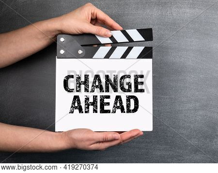 Change Ahead. White Movie Clapper In Woman Hand On Chalkboard Background