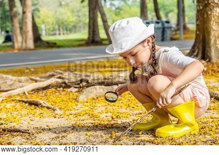 Image Of Cute Girl Exploring The Nature With Magnifying Glass Outdoors, Child Playing In The Forest