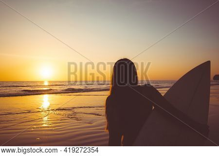 Silhouette Of Beautiful Sexy Surfer Female With Surfboard On The Sandy Beach At Sunset. Water Sports