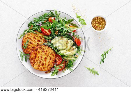 Grilled Chicken Burgers, Avocado And Fresh Vegetable Salad With Tomato And Arugula