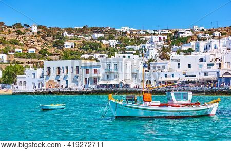 Mykonos, Greece - April 22, 2018:  View with seafront and fishing boat in Mykonos (Chora) town