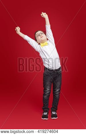 Full Body Of Little Nerd Boy In White Shirt With Bow Tie And Glasses Reaching Arms Up While Standing