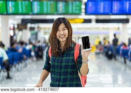 Asian Traveler With Luggage Showing The Smart Mobile Phone For Check-in Over The Flight Board At The