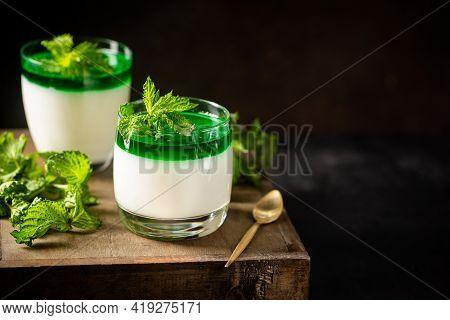 Dessert Panna Cotta With Green Mint Sauce And Fresh Mint On Dark Background
