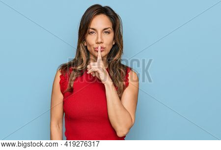 Young hispanic woman wearing casual clothes asking to be quiet with finger on lips. silence and secret concept.