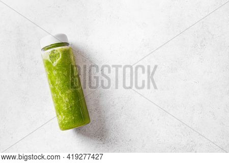 Green Smoothie In Plastic Bottle On White, Top View, Copy Space. Fresh Raw Detox Smoothie Or Green J