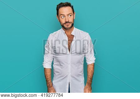 Middle age man wearing casual clothes smiling looking to the side and staring away thinking.