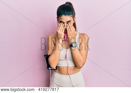 Young hispanic woman wearing gym clothes and using headphones rubbing eyes for fatigue and headache, sleepy and tired expression. vision problem