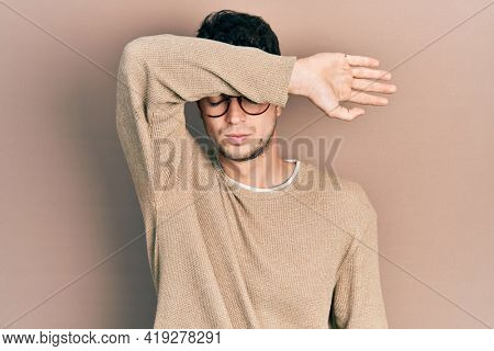 Young hispanic man wearing casual clothes and glasses covering eyes with arm, looking serious and sad. sightless, hiding and rejection concept