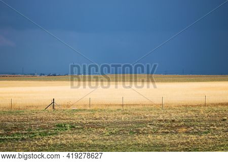 Rustic Fence Besides Rural Grasslands On A Ranch Surrounded By Thunderstorm Clouds And Heavy Rain In