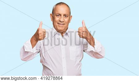 Handsome senior man wearing elegant white shirt success sign doing positive gesture with hand, thumbs up smiling and happy. cheerful expression and winner gesture.