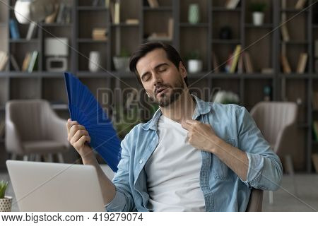 Exhausted Businessman Waving Paper Fan, Sitting At Desk With Laptop