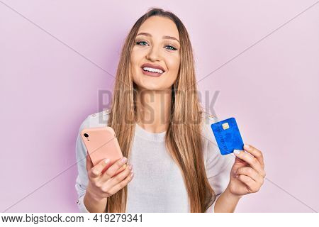 Young blonde girl holding smartphone and credit card smiling and laughing hard out loud because funny crazy joke.
