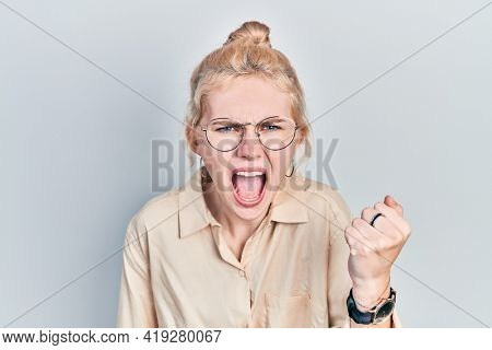 Beautiful caucasian woman with blond hair wearing casual look and glasses angry and mad raising fist frustrated and furious while shouting with anger. rage and aggressive concept.