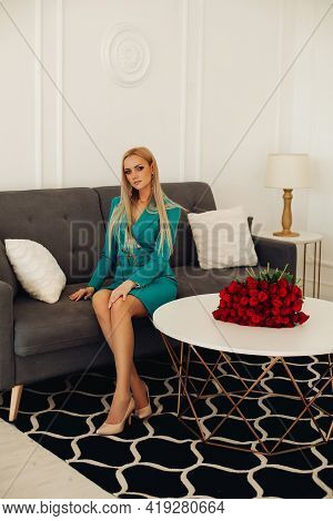 Posh Blonde On Sofa In Living Room With Bouquet.