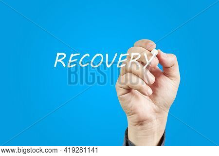 Hand Of Man Writing The Word Recovery On A Blue Background. Recovery Concept