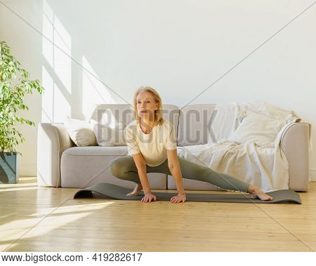 Beautiful Healthy Mature 60s Women In Sports Wear Doing Stretching Exercises On Yoga Mat In Living R