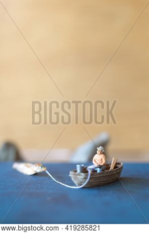 Miniature People, Miniature Fishermen Are Fishing By Boat