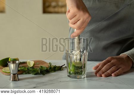 Bartender Prepares A Cocktail Mojito Using The Madler. Bartender Crushes Mint And Lime With A Madler