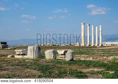 Remains Of Columns & Its Capitals With Ornaments. Colonnaded Street Is On Background. Shot In Ancien