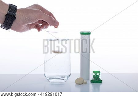 Throw The Pill Into A Glass Of Water. Throw Vitamins Into Water. Hand Throwing A Pill. Front View.