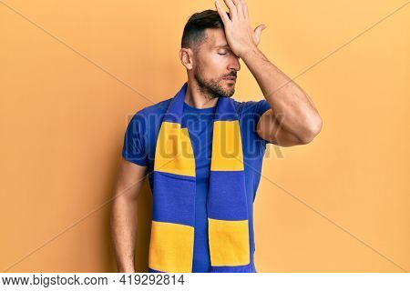 Handsome man with beard football hooligan cheering game surprised with hand on head for mistake, remember error. forgot, bad memory concept.