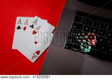 Poker Cards, Stacks Of Poker Chips And Laptop On A Red Background. Poker Online Concept