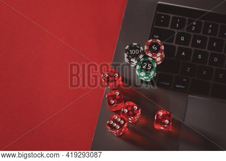Stacks Of Poker Chips, Dices And Laptop On A Red Background. Poker Online Concept