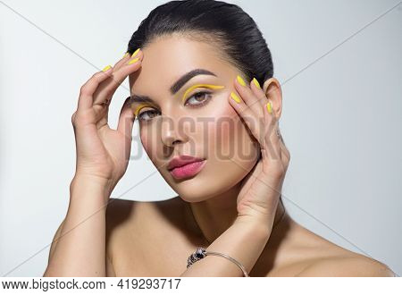 Beauty model girl with fashion make-up, Bright yellow eye line and nails, trendy manicure. Eye make-up creative ideas. Summer makeup. Beautiful young woman portrait. Face closeup