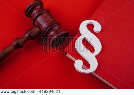 Paragraph Symbol Is On A Book And Gavel On Red Background. Law And Justice Concept