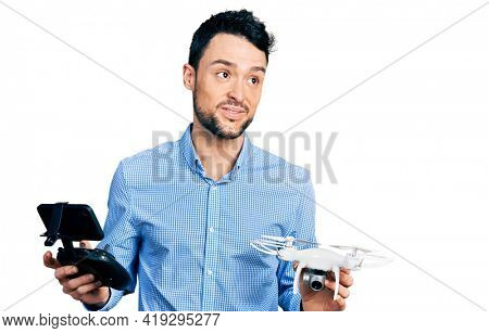 Hispanic man with beard using drone with remote control smiling looking to the side and staring away thinking.