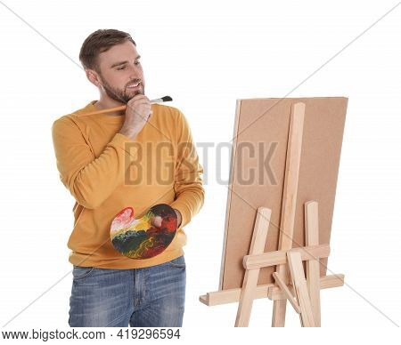 Man Painting With Brush On Easel Against White Background. Young Artist