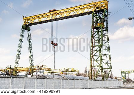 Large Industrial Crane. Crane For Lifting Large Loads. The Crane Is Behind The Fence. Front View.
