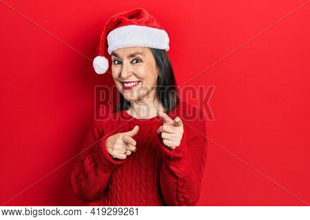 Middle age hispanic woman wearing christmas hat pointing fingers to camera with happy and funny face. good energy and vibes.