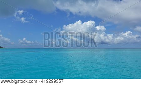 The Aquamarine Ocean Is Calm. There Are Picturesque Cumulus Clouds In The Azure Sky. Summer Sunny Da