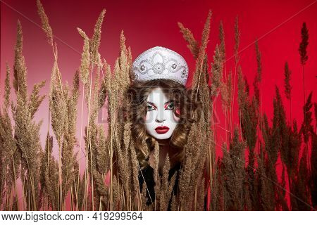Fashion Russian Woman In A Kokoshnik With Samovar On Red Background, Bright Makeup, Make-up On Woman