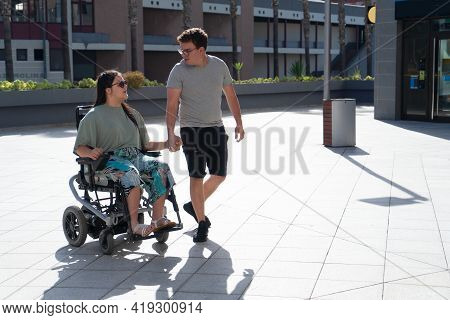 Young Disabled Woman In Wheelchair And Her Loving Boyfriend Or Husband Holding Hands And Looking At
