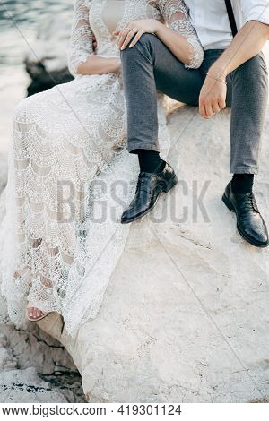 Bride And Groom Are Sitting On A Large Stone On The Coast. Bride Put Her Hands On The Knees Of Groom