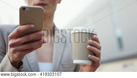 Close Up Of The Famale Hand Scrolling And Taping On The Smartphone. Blonde Woman In Glasses Drinking