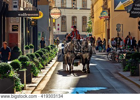 VIENNA, AUSTRIA - SEPTEMBER 27, 2018: Tourist horse-drawn carriage rides on narrow street in historic part of Vienna - capital city, famous and popular tourist destination.