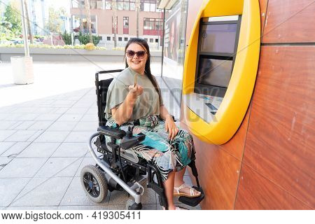Young Happy Disabled Handicapped Woman In Wheelchair Using Atm Cash Macjine And Smiling At Camera On