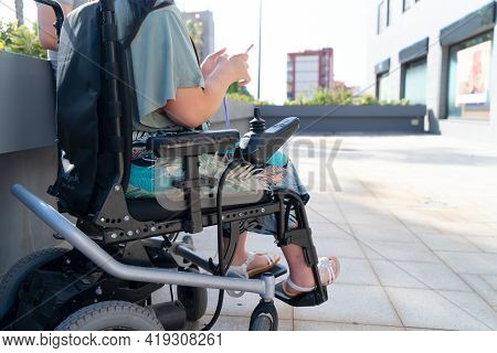 Disabled Handicapped Woman In Wheelchair Using Smartphone And Smiling At Camera While Walking Outdoo