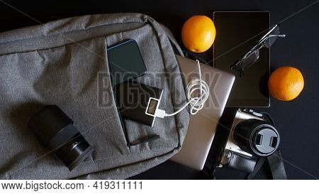 Mirrorless Camera, Laptop, Smartphone, Power Bank And Other Modern Gadgets In A Trendy Gray City Bac