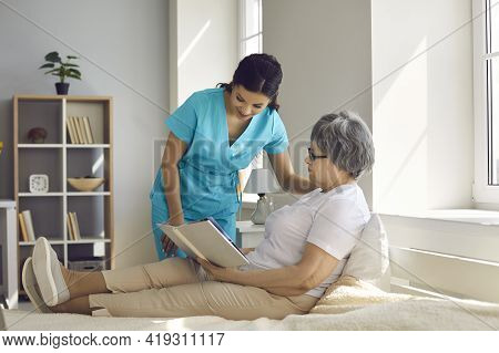 Home Care Nurse Talking To Relaxed Senior Woman Whos Sitting On Bed And Reading Book