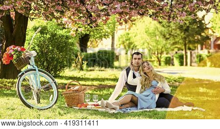 Couple Date On Blanket Under Sakura Flowers. Camping. Happy Couple In Love. Woman And Man Lying In P